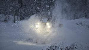 En traktor med snöplog och snö som ur omkring dem.