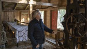 En man står vid ett gammalt sågverk (delar av) inne i ett gammalt hus.