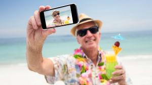 Leende äldre man tar selfie på strand