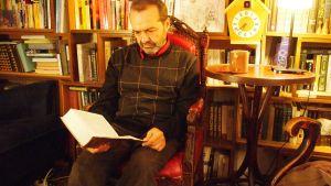 Shenderovich lukee kirjaa kirjastohuoneessa