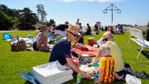 Människor sitter på gräset och har picknick. I bakgrunden skymtar en midsommarstång.