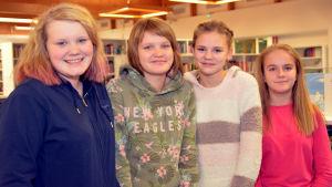 Fyra flickor poserar i Ingå bibliotek. De heter Lina och Emilia Löflund, Julia Wikman och Linda Österman.