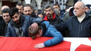 En man särjer böjd över en kista andra män tröstar honom.
