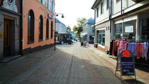 """En bild på en folktom gågata. På höger sida står en skylt med texten """"slutförsäljning""""."""
