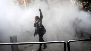 Demonstrant står bland tårgas med lyft knuten näve.