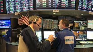 Två aktiemäklare vid dagens slut, med stora datorskärmar som visar kurshändelser+Donald Trump på TV.