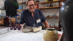 Antikhandlare Lennart Andersson sitt vid ett bord med lockfåglar framför sig.