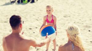 En flicka leker på stranden med sina föräldrar.