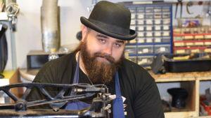 En skäggprydd man med plommonstop (hatt) på huvudet. Sitter bakom en gammal symaskin.