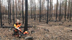 En skogsarbetare i skyddsutrustning sitter på marken i en skog av svarta nerbrunna stammar.