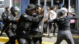Kravallpolis föser iväg folk under en räd i Managua
