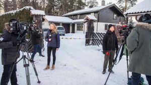 Två journalister utanför ett hus filmas av tv-kameror.