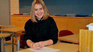 Frida Läckström sitter vid pulpeten och skriver. Hon ler mot kameran.