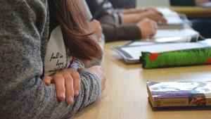 personers armar på bord i undervisningsklass