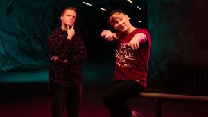 Mikael Stenlund står i en fundersam pose med Kristian Westerling brevid sig. Kristian sitter på ett metallräcke och pekar in i kameran med båda fingrarna. De befinner sig i en källargång och ljuset är dunkelt med kontrast av magenta c guldgula effektljus