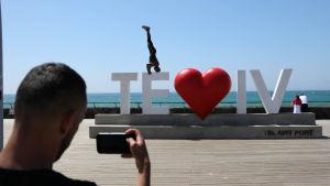 """en man tar en bild på en person som stå på huvudet på en stor namnskylt där det står """"te - iv"""" med ett hjärta i mitten."""