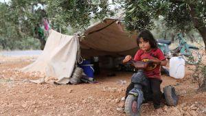 Ett barn som flytt undan striderna i södra Idlib leker utanför ett tält