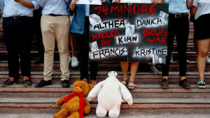 Demonstranter demonstrerar på en trappa där man lagt ut gosedjur. På ett av plakaten står det namn på unga personer som dött på grund av kriget mot droger.