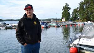 En man står på en brygga framför en båthamn.