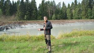En man står invid en stor bassäng, sedimenteringsbassäng.