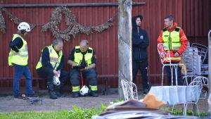 Räddningsverkspersonal vid en husvägg.
