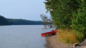 Sibboviken samt en roddbåt som dragits upp på stranden.