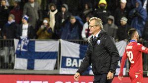Markku Kanerva går på en fotbollsplan. I bakgrunden syns Finlands flagga, något ur fokus.