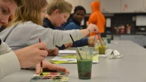Flera elever sitter på rad och målar och pratar.