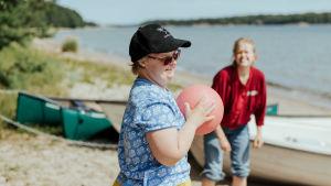 två personer kastar boll på stranden