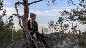 Mathilda Sjöblom sitter på ett berg.