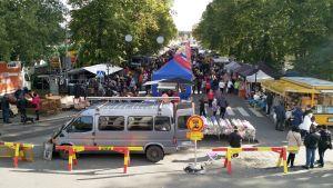 En gata fylld med människor och marknadsstånd.