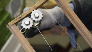 Närbild på en träram med två vajrar. Carolina håller ett verktyg i handen som ska spänna vajern.