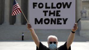 """En man med munskydd och glasögon håller upp en skylt med texten """"Follow the money"""" (""""Följ pengarna"""") och USA:s flagga."""