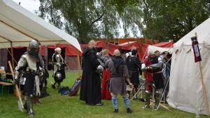 Män och kvinnor i rustningar står utanför vitt tält på gräsmatta. I förgrunden en man i riddarrustning som bär på en yxa.