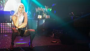 Person i hukande ställning på höga klackar, personen står på ett dansgolv som är upplyst i flera färger.