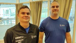 Portättbild på två män, Patrik Nyberg och Benny Forsström,  klädda i sportjacka respektive t-skjorta. Bakom stora fönster (i bakgrunden) ser man Ekenäs simhall med sina bassänger.