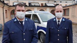 Två poliser, Tobias Karlsson och Fred Lindblom, står i paraduniform framför en polisbil.