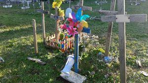 Vindsnurror och blommor vid några träfärgade kors.
