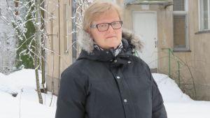 En kvinna med kort blont hår och glasögon står ute på en gård.  Hon är klädd i vinterjacka. Snö och i bakgrunden ett hus med brungrå rappning.
