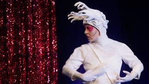 Drag-artisti Theodora Rex pukeutuneena valkoiseen asuun, jonka hupussa valkoisia tekokäsiä.