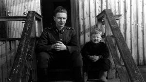 TK-kuvaaja Eino Nurmi sisarensa Kerttu Rosenlöfin pojan kanssa tämän kotitalon portailla 1942.