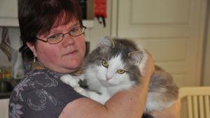 Camilla Hautaviita står med katten Wilma i famnen