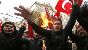 Anhängare av president Recep Tayyip Erdoğan brände upp en amerikansk dollar och skrek slagord mot Nederländerna utanför det holländska konsulatet i Istanbul den 12 mars 2017.