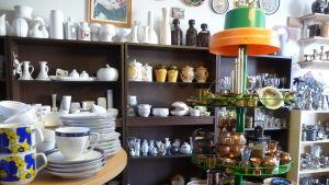 Loppissaker på hyllor, bland annat kaffekoppar, vaser, skålar, kopparföremål med mea.