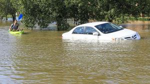 En man paddlar förbi en sjunkande bil efter att stormen Harvey orsakade översvämningar i Houston.