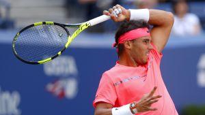 Rafael Nadal grimaserar med en tennisracket ovanför huvudet.