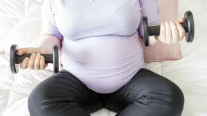 raskaana oleva nainen nostaa pieniä puntteja