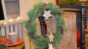 En krans av tallris dekorerad med kottar och stjärnanis.