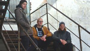 Festivalarrangörer Fredrik Öblom, Jens Heinström och Alfons Grönqvist på en trappa i Stora smedjan vid Billnäs bruk.