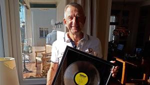 Producenten Bengt Palmers med en diamatskiva i sitt hem på Lidingö